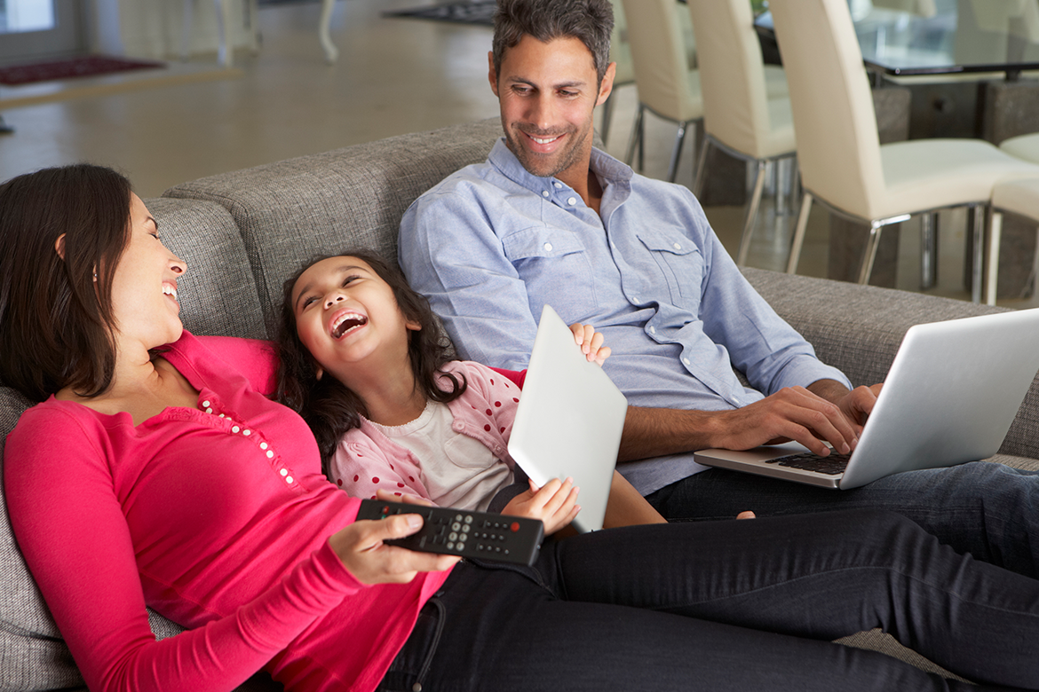 Family relaxing on couch viewing tablet in energy efficient home